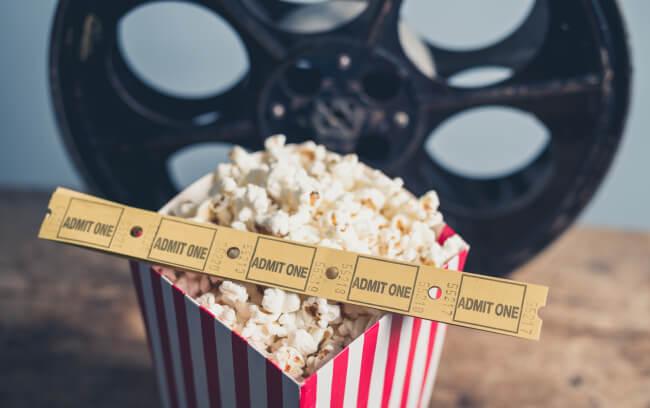 Old film reel, popcorn, cinema tickets
