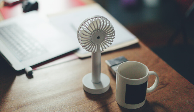 Tiny fan and mug on desk