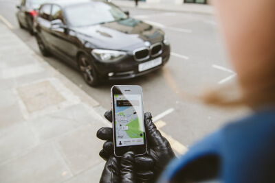 Woman waiting for uber car with app 400