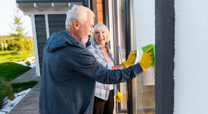 Elderly couple cleaning window